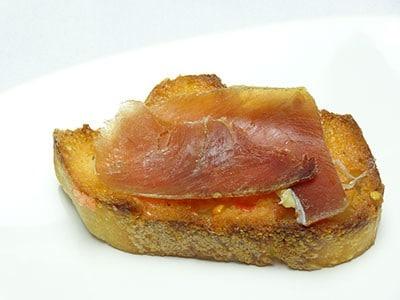 Tapas, montadito de pan tomate avec jambon serrano réalisé par Paellas de José